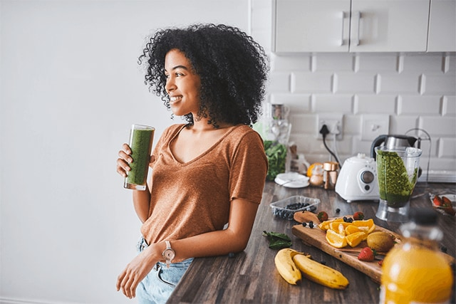 Woman at counter with immune supporting smoothie and nutrient-dense foods